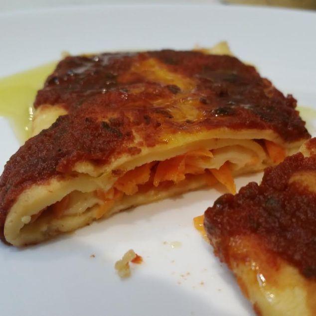 Crepioca com queijo lacto free, cenoura ralada e molho de tomate por cima.